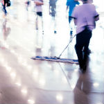 Houston commercial cleaning services worker dusting floor during working hours